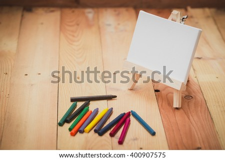 Crayon with paint canvas on wood background with copy space - stock photo