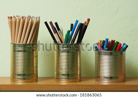 Crayons and pens in waste tin cans standing on a shelf. - stock photo