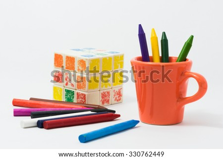 crayons full color with small cup and toys for the child. - stock photo