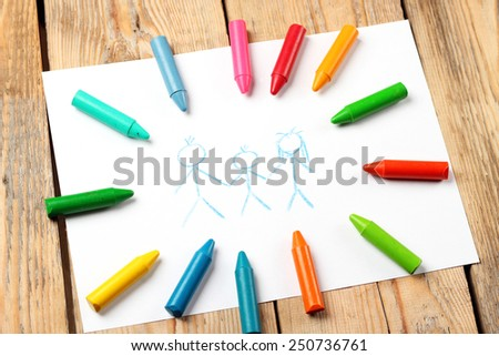 Crayons lying on a paper with children's drawing family. Selective focus - stock photo