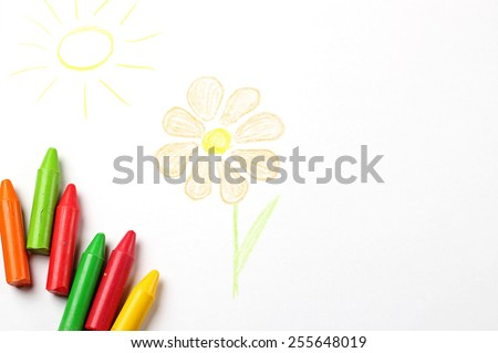 Crayons lying on a paper with children's drawing flower and sun. Selective focus, copy space background, top view - stock photo