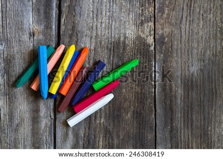 crayons on old rustic wooden background - stock photo