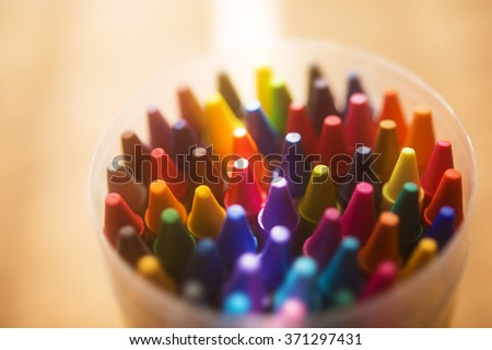 Crayons shot from above with incoming light. Extremely shallow depth of field for dreamy impressional feel .Soft focus filter used. - stock photo