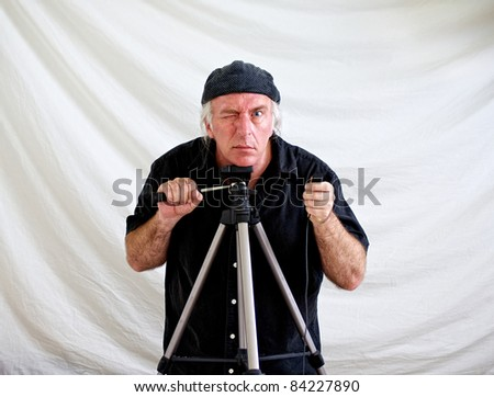 Crazed looking man resting head on tripod and holding shutter release in hand looking intently at viewer while other hand holds tilt arm of tripod. - stock photo