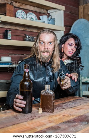 Crazed Western Man Aims Gun Towards You as he Sits at Table With Woman