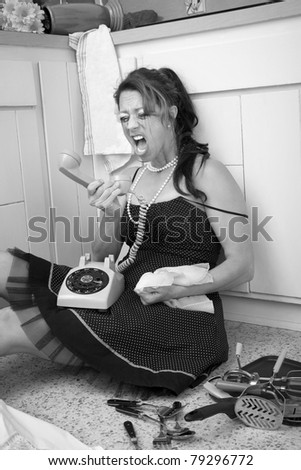Crazed woman sitting on the kitchen floor yells at her telephone