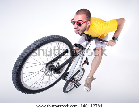 crazy boy on a dirt jump bike making funny faces- wide studio shot - stock photo