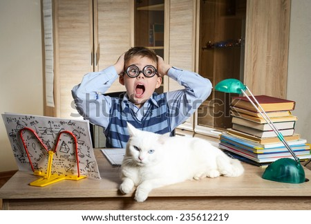 Crazy Boy Wearing Funny Glasses Doing Homework With Cat Sitting On The Desk. Child With Learning Difficulties. Boy Having Problems With His Homework. Panic. Education Concept. - stock photo