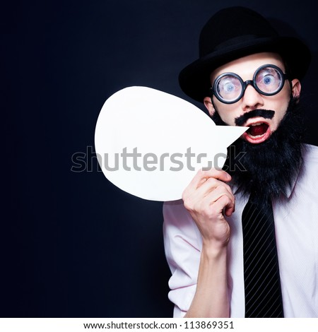 Crazy Business Man In Fake Beard And Nerd Glasses Holding Copyspace Speech Bubble While Marketing Business Specials On Dark Background - stock photo