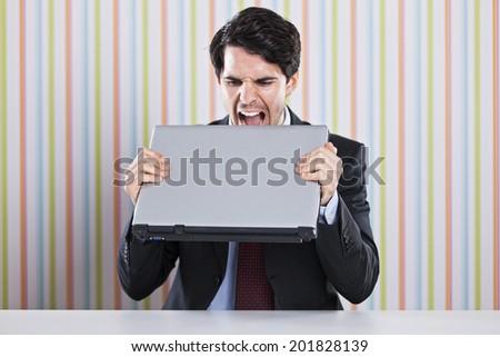 Crazy businessman eating his laptop - stock photo