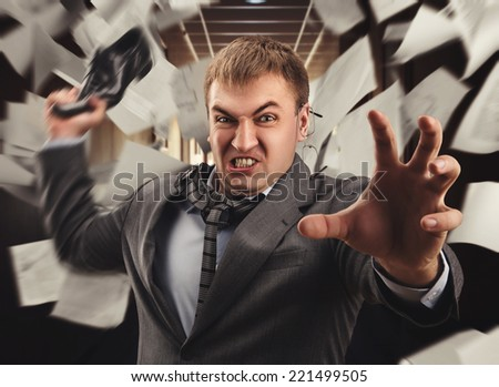 Crazy businessman is fighting in office - stock photo