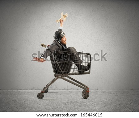 Crazy businessman play with a wooden toy like a child - stock photo