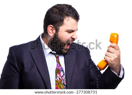 Crazy businessman shouting to a vintage telephone - stock photo