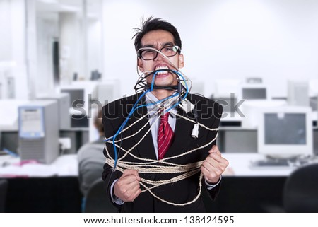 Crazy businessman tied in cable and rope at office - stock photo