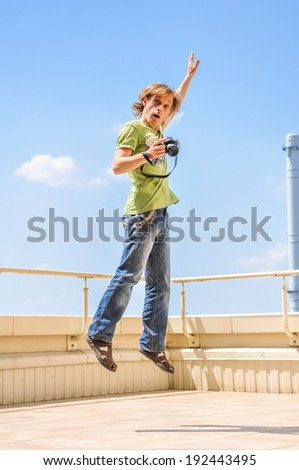 crazy cheerful photographer in jump - stock photo
