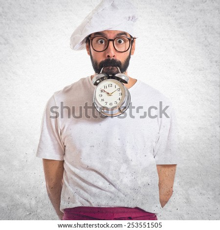 Crazy chef holding a clock over white background - stock photo
