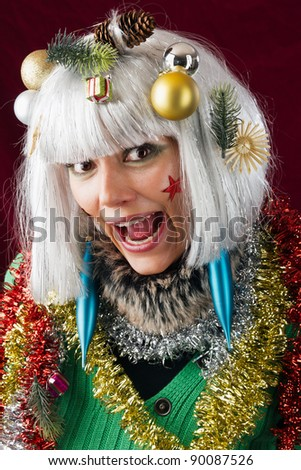 Crazy Christmas woman. Studio shot against a red background. - stock photo