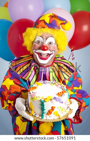 Crazy clown with balloons, holding a birthday cake. - stock photo