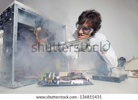Crazy computer technician is trying to repair a computer with a drill - stock photo