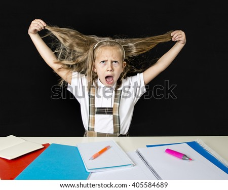crazy cute junior schoolgirl sitting on desk in stress working doing homework pulling her blond hair crazy and overwhelmed in children education and school hard work - stock photo