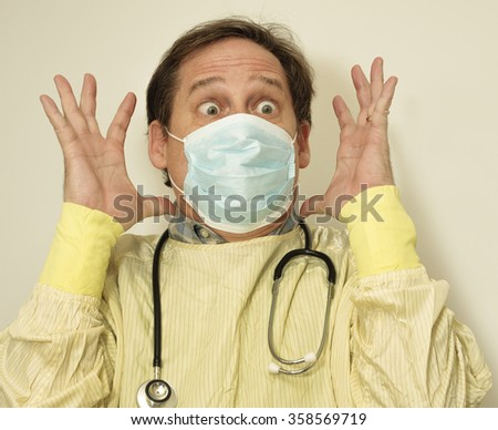 Crazy doctor in yellow infection control robe is wide eyed and has his hands up - stock photo