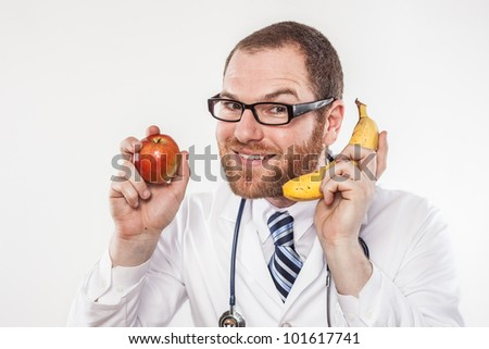 Crazy doctor man holding banana and apple while staring through glasses at someone