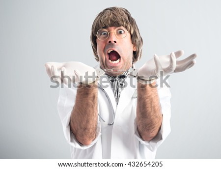 Crazy doctor with handcuffs over grey background - stock photo