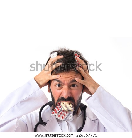 Crazy doctor with pills over white background - stock photo