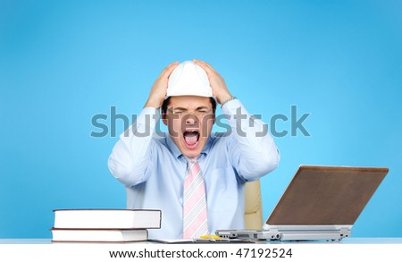 Crazy engineer with white hard hat at work on blue background - stock photo