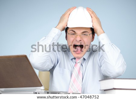 Crazy engineer with white hard hat at work on gray background - stock photo