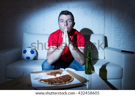 crazy fanatic man football fan watching football game on television wearing red team jersey suffering nervous and stress praying god on sofa couch at home with soccer ball beer bottle and pizza - stock photo