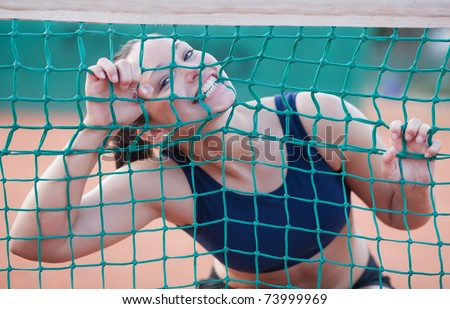 Crazy female tennis player biting the net