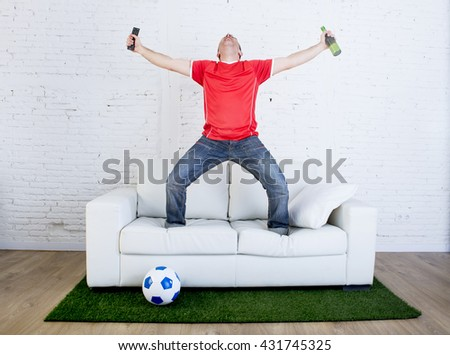 crazy football fan in red team jersey cheering happy watching television soccer match celebrating scoring goal excited and euphoric in sofa couch with ball on grass carpet emulating stadium pitch - stock photo
