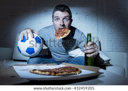 crazy football fan man watching soccer game on television at home sofa couch with soccer ball and pizza in his mouth holding beer bottle looking anxious nervous and suffering stress - stock photo