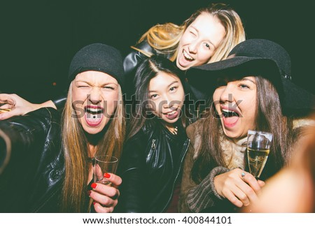 Crazy friends taking selfie in a bar with smart phone - stock photo