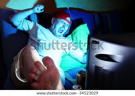 Crazy fun watching sports match by TV - stock photo