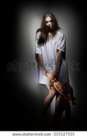 Crazy girl with plastic doll - stock photo