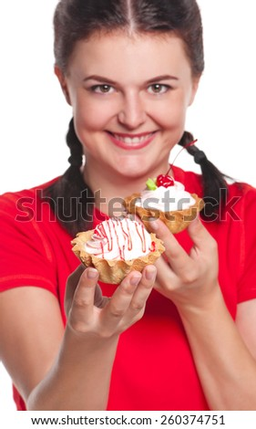 Crazy greedy girl with cakes isolated on white background. Focus on the first cake - stock photo