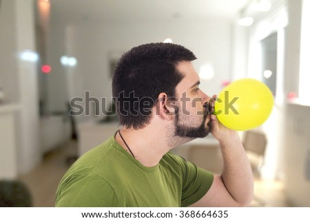 Crazy guy blowing green balloon - stock photo