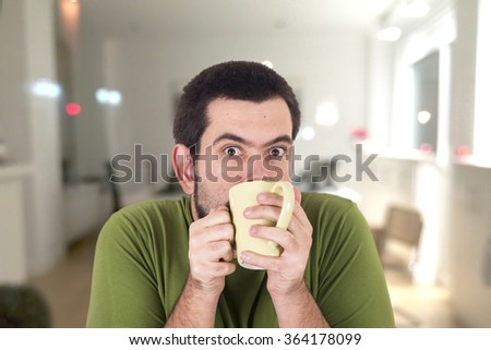 Crazy guy drinking with cup - stock photo
