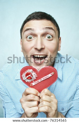 Crazy happy guy holding red valentine card with hugs and kisses ribbon - stock photo