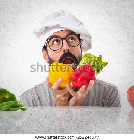 Crazy hipster chef playing with vegetables - stock photo