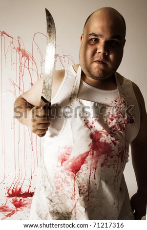 Crazy insane butcher covered with blood.  Harsh lighting for more disturbing feel. - stock photo