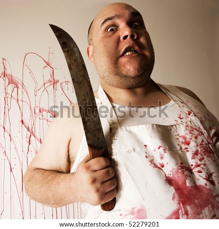 Crazy insane butcher covered with blood.  Harsh lighting from below for more disturbing feel. - stock photo