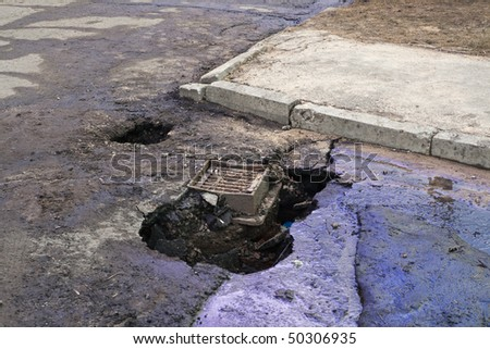 Crazy Latvian roads series: huge potholes in asphalt near manhole with poured oil. - stock photo
