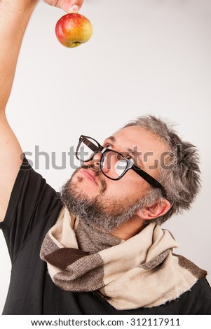 Crazy looking grumpy old man with grey beard nerd big glasses funny looking up on apple in his hand - stock photo