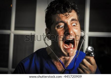 Crazy lunatic male nurse yells into his own stethoscope - stock photo