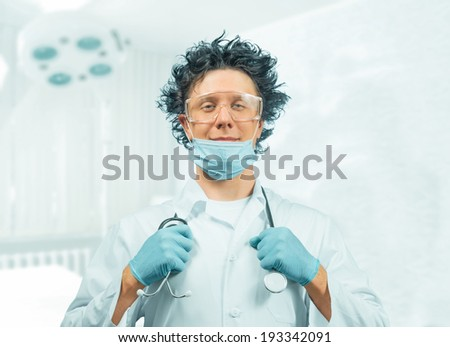 Crazy man doctor is holding stethoscope on a hospital - stock photo