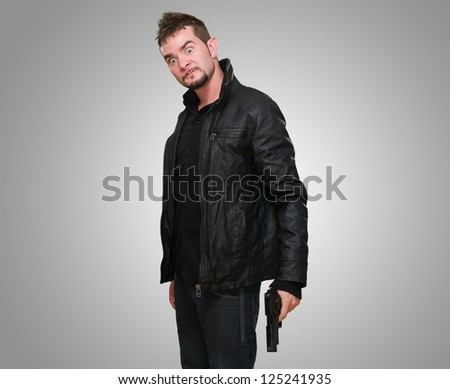 crazy man holding a gun against a grey background