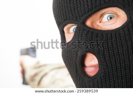 Crazy man in black mask holding gun - stock photo